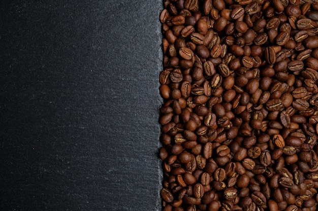 Background from coffee beans and slate for copy space. top view.