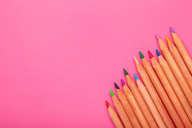 コピースペースのあるピンクの紙に色鉛筆の背景。上面図