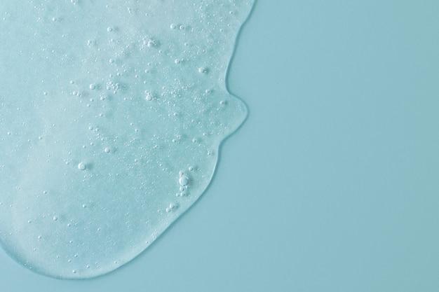 거품이 떨어지는 화장품 젤의 배경밝은 파란색 색상 복사 공간
