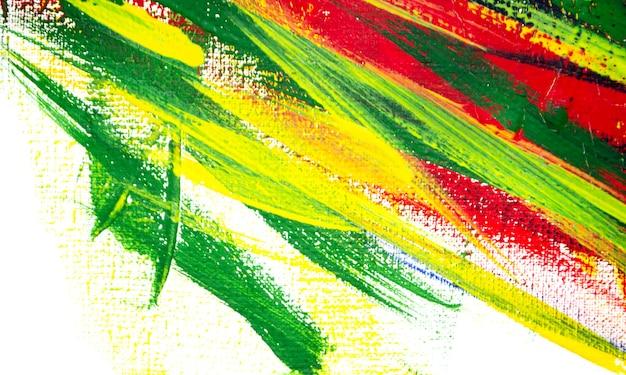 Фон из различных мазков красной, желтой, зеленой и синей краской с кистью на белом фоне крупным планом. яркий красочный фон из линий кисти. смешивание цветных полос краски на белом холсте