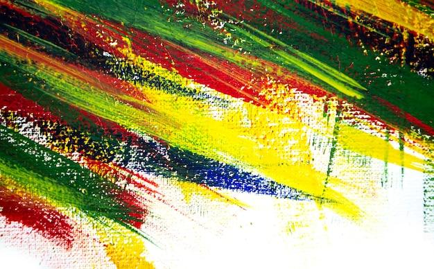 Фон из различных мазков красной, желтой, зеленой и синей краской с кистью на белом фоне крупным планом. яркий красочный фон из линий кисти. v цветные полосы краски на белом холсте