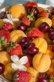 新鮮なベリーや果物の背景-アプリコット、イチゴ、さくらんぼのクローズアップ