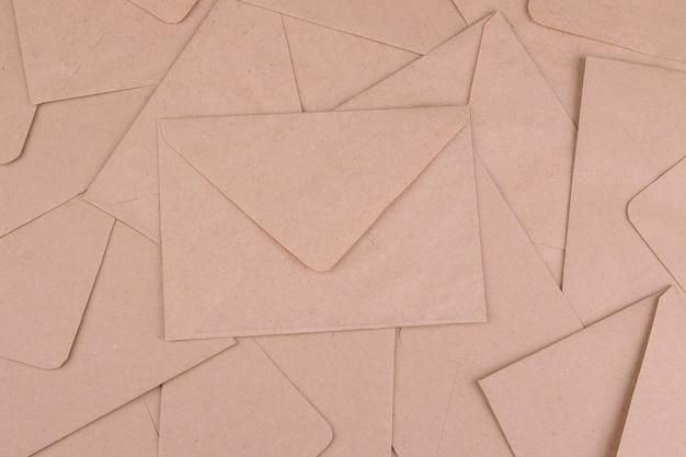 Фон из почтовых конвертов из крафт-бумаги. вид сверху. концепция почты или доставки