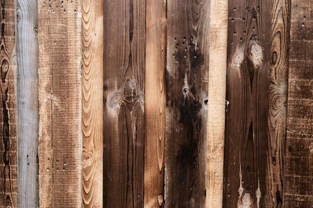 古い木の部分からの背景。自然な木の質感。古いフェンス。茶色の古い木製のフェンス。ダークウッド。