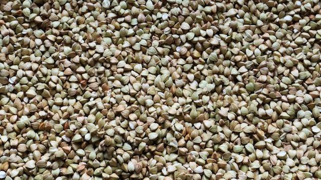 Фон из сырой органической зеленой гречневой каши, веганской еды. текстура рассыпанной гречневой крупы. семена имеют треугольную форму. органическая еда. концепция диеты, похудания, здорового питания.