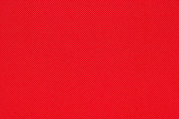 小さなひし形のキャンバス不織布素材の赤い色のテクスチャからの背景。空白の明るい抽象的なパターンの背景のクローズアップ表面、テキストとコピースペースの準備ができています。
