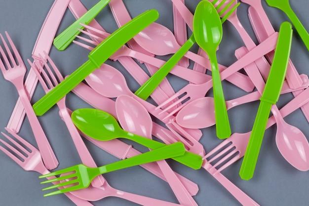 재사용 가능한 재활용 분홍색과 녹색 포크, 숟가락, 회색 종이에 옥수수 전분으로 만든 칼의 배경.