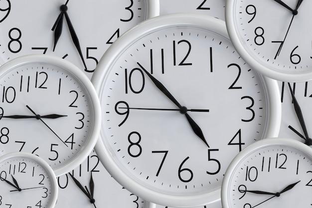 Фон из набора белых аналоговых круглых офисных часов разных размеров, показывающих разное время