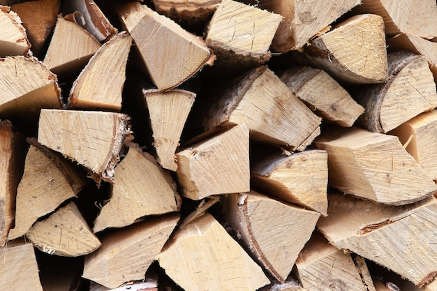 Background from stack of firewood from birch tree, for heating house, stacked in backyard, uncut wood, birch.