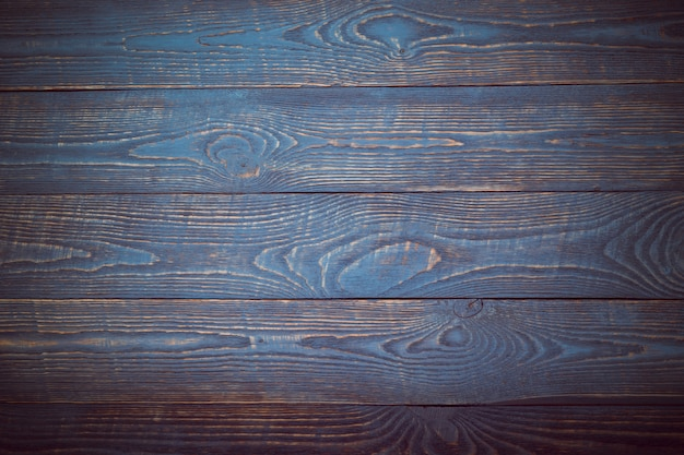 Background from wooden texture boards with remnants of blue and violet paint. vignetting