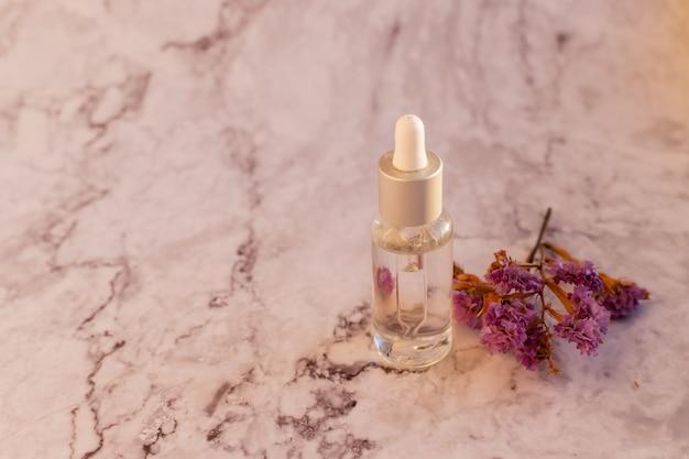 Композиция с фиолетовыми цветами лимониума, натуральными косметическими продуктами на мраморной предпосылке background.glass и различными органическими травами.