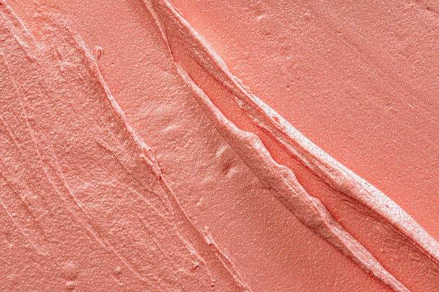 Background of a glossy smudged peach color lipstick