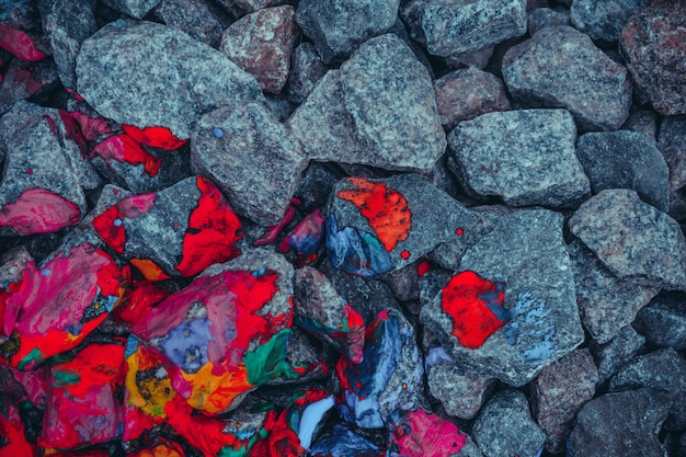 Background gray stones and rocks painted in mottled red, view from above