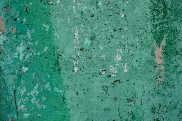 Background of green textured shabby wall with stains of paint and holes in daylight.