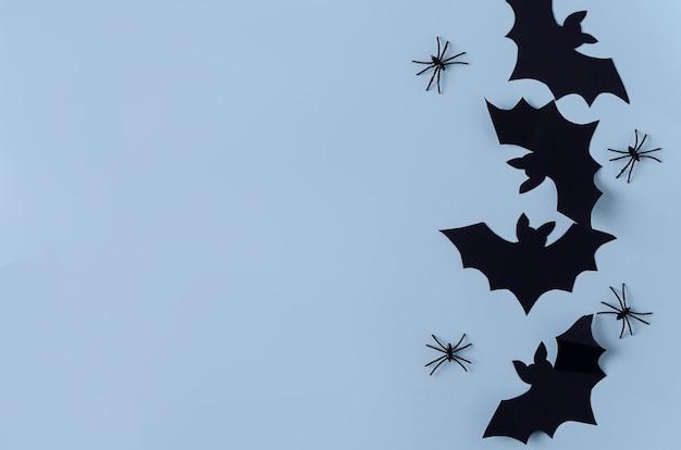 背景ハロウィーン。紙のコウモリとクモは黒い背景、コピースペース、フラットなレイアウトにあります