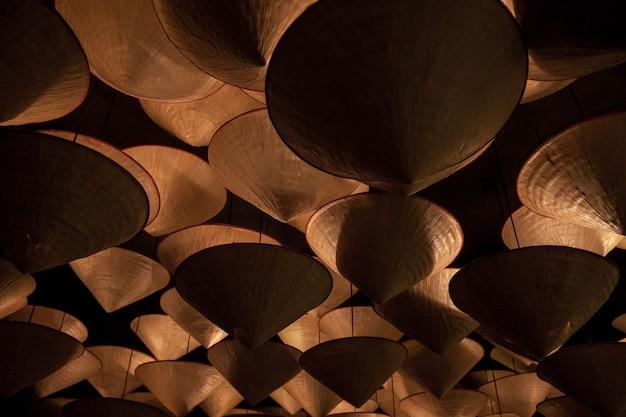 未来的な光のための円錐形のランプシェードからの背景の手作りのシャンデリア。天井の下の木製のシャンデリア。抽象的なシャンデリア。装飾的な天井。背景の概念。テキスト用のスペースをコピーする