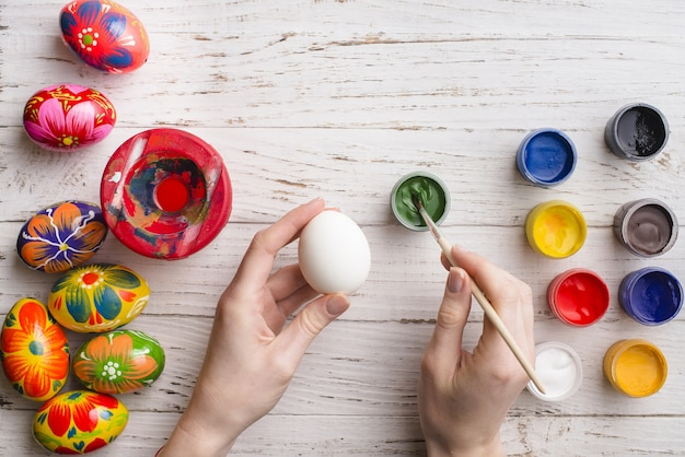 Background of hands with eggs and paint jars