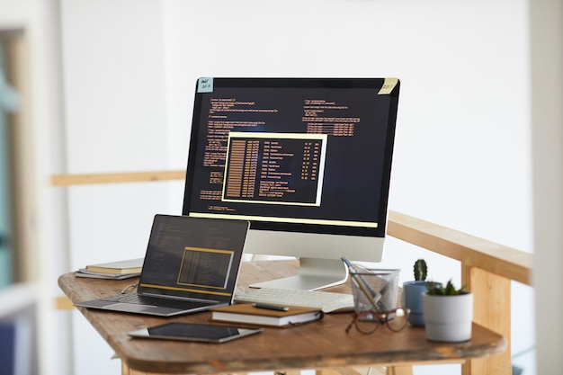 Background image of black and orange programming code on computer screen and digital devices in modern white office interior, copy space