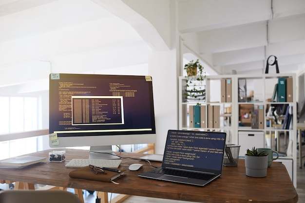 Background image of black and orange programming code on computer screen and laptop in contemporary office interior, copy space