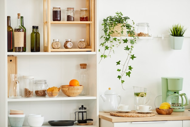 Background image of cozy kitchen interior with wooden shelves for spices and utencils decorated with plants, copy space
