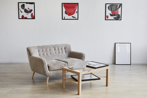 Background image of designer interior with couch and coffee table decorated by modern abstract paintings on wall,
