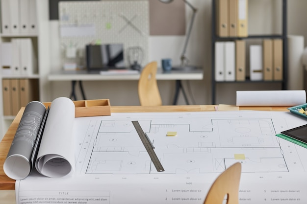 Background image of drawing table with blueprints and tools laid out in forground and architects workplace,