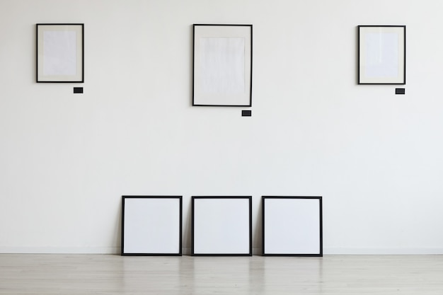 Background image of empty black frames hanging on white wall at art gallery,