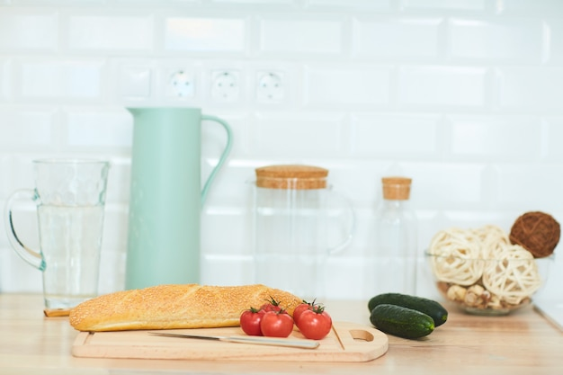 Background image of healthy food ingredients on wooden kitchen counter against white wall, copy space