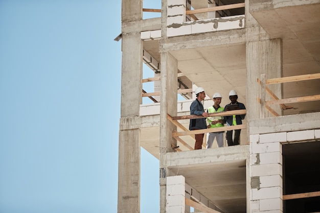 Background image of high rise construction site with group of workers copy space