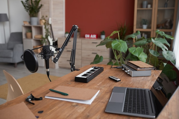 Background image of home recording studio with music equipment and laptop on desk, copy space