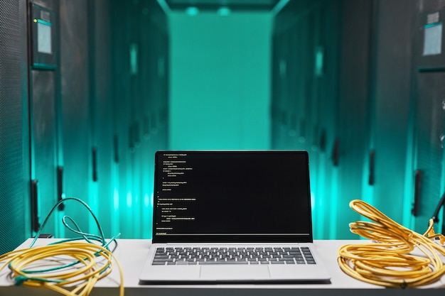 Background image of laptop with code on screen in server room, copy space