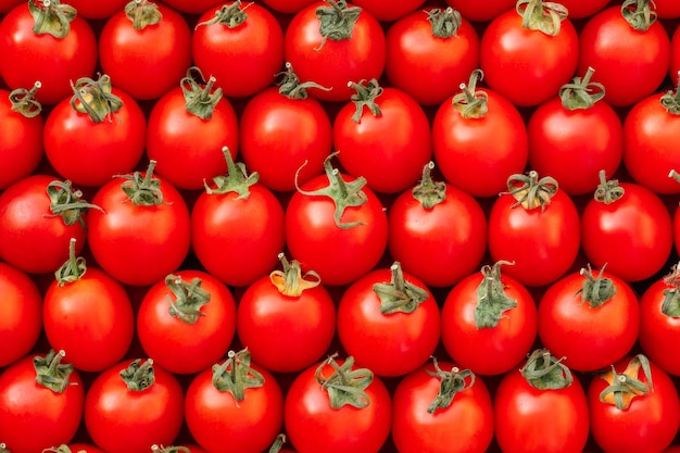 Background image of lying rows of red ripe cherry tomatoes. top view. flat lay, copy space