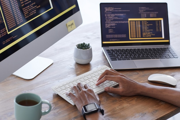 Background image of male hands typing on keyboard while working on computer code in it development studio, copy space
