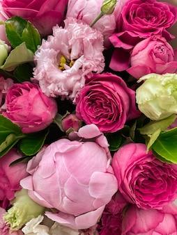 Фоновое изображение нежного букета цветов. в цветочной композиции сочетаются розовые пионы, яркие розы, эустома и зелень. романтический подарок на праздник. открытка с цветами крупным планом