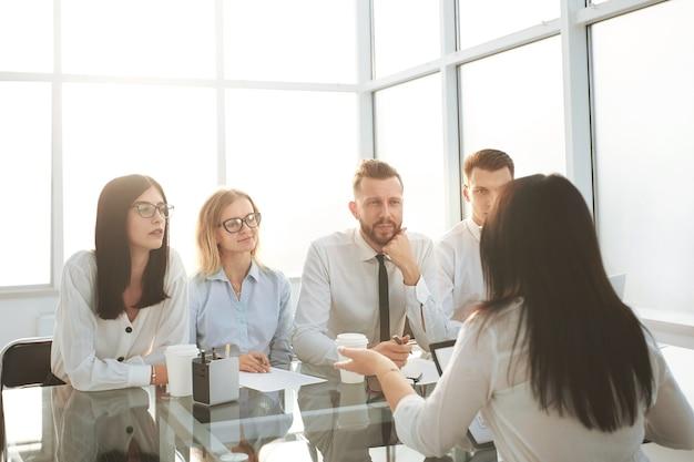 책상에 앉아 있는 비즈니스 사람들의 그룹의 배경 이미지입니다. 복사 공간이 있는 사진
