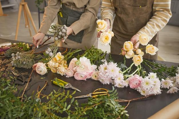 花束、コピースペースを配置する2人の認識できない花屋とフラワーショップのテーブルの上の美しい花の背景画像