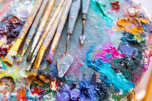 Фоновое изображение ярких красок смешанного цвета на художественной палитре с кистями и мастихином
