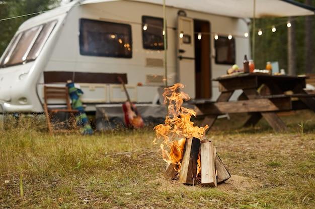 背景のコピースペースにトレーラーバンがある森のキャンプファイヤーの背景画像