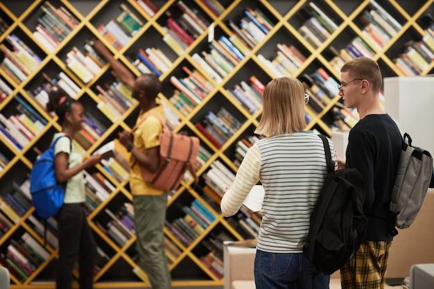 バックパックのコピースペースを運ぶ若い学生と大学図書館の背景画像