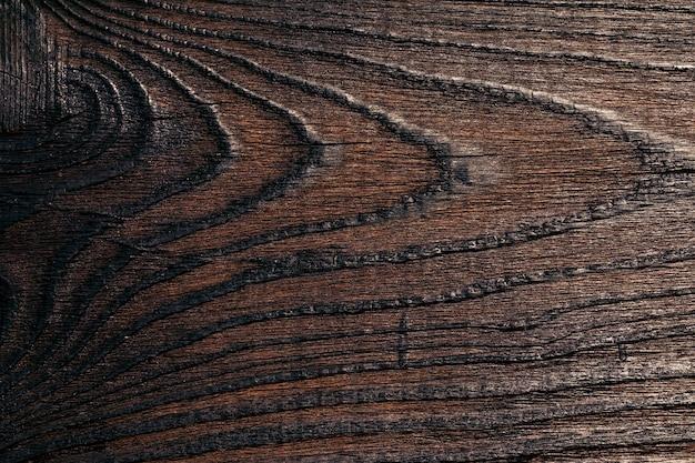 ダークウッドテクスチャの背景画像。建設および仕上げ作業、家具製造用の大規模なパターンの繊維を備えた漆塗りの板。テクスチャ要素。