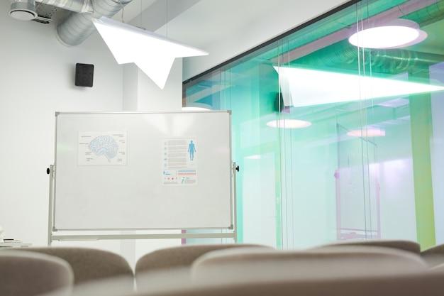 Фоновое изображение пустой аудитории с набором доской для презентации в коворкинг-центре, копией пространства