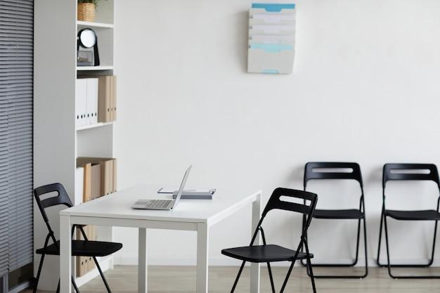 Фоновое изображение пустого кабинета врачей со столом и стульями в ряду, копией пространства