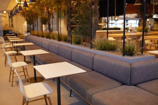 ショッピングモール、コピースペースで単一の座席テーブルと空のフードコートのインテリアの背景画像