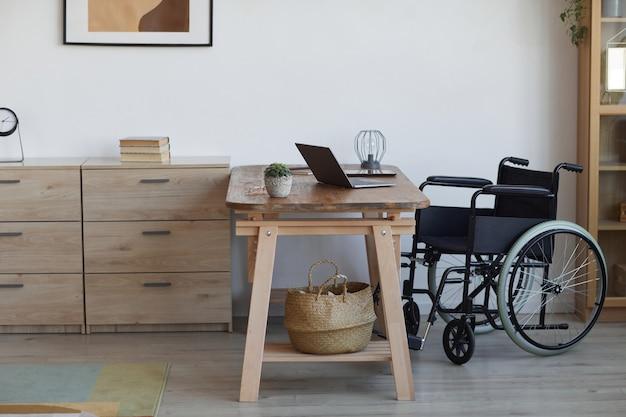 アクセシブルなホームオフィスの職場、コピースペースの机のそばの空の車椅子の背景画像