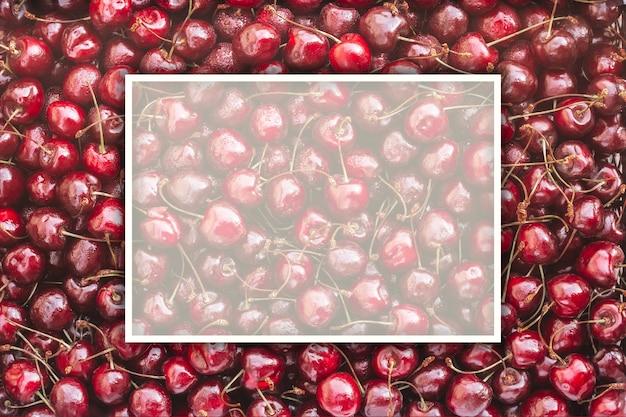 Фоновое изображение лежащих красных спелых черешен с белой прямоугольной рамкой. вид сверху, плоская планировка. копировать пространство