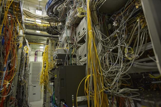 Фоновое изображение грязной серверной комнаты с кучей интернет-кабелей и проводов, копией пространства