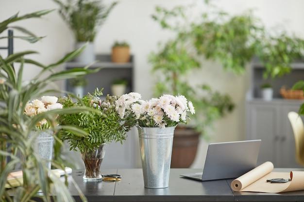 Фоновое изображение минимальных цветочных композиций в деревенских металлических ведрах на столе в зеленой мастерской флористов, копировальное пространство