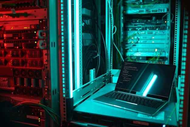 데이터 센터의 서버 캐비닛에 의해 열린 노트북의 배경 이미지, 파란색 조명, 복사 공간