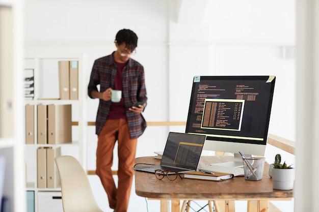 Фоновое изображение программного кода на экране компьютера в интерьере современного офиса с размытой формой афроамериканца, копией пространства