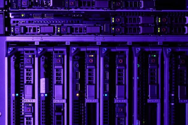 파란색과 보라색 빛으로 켜진 슈퍼컴퓨터 네트워크의 랙 서버 배경 이미지, 복사 공간